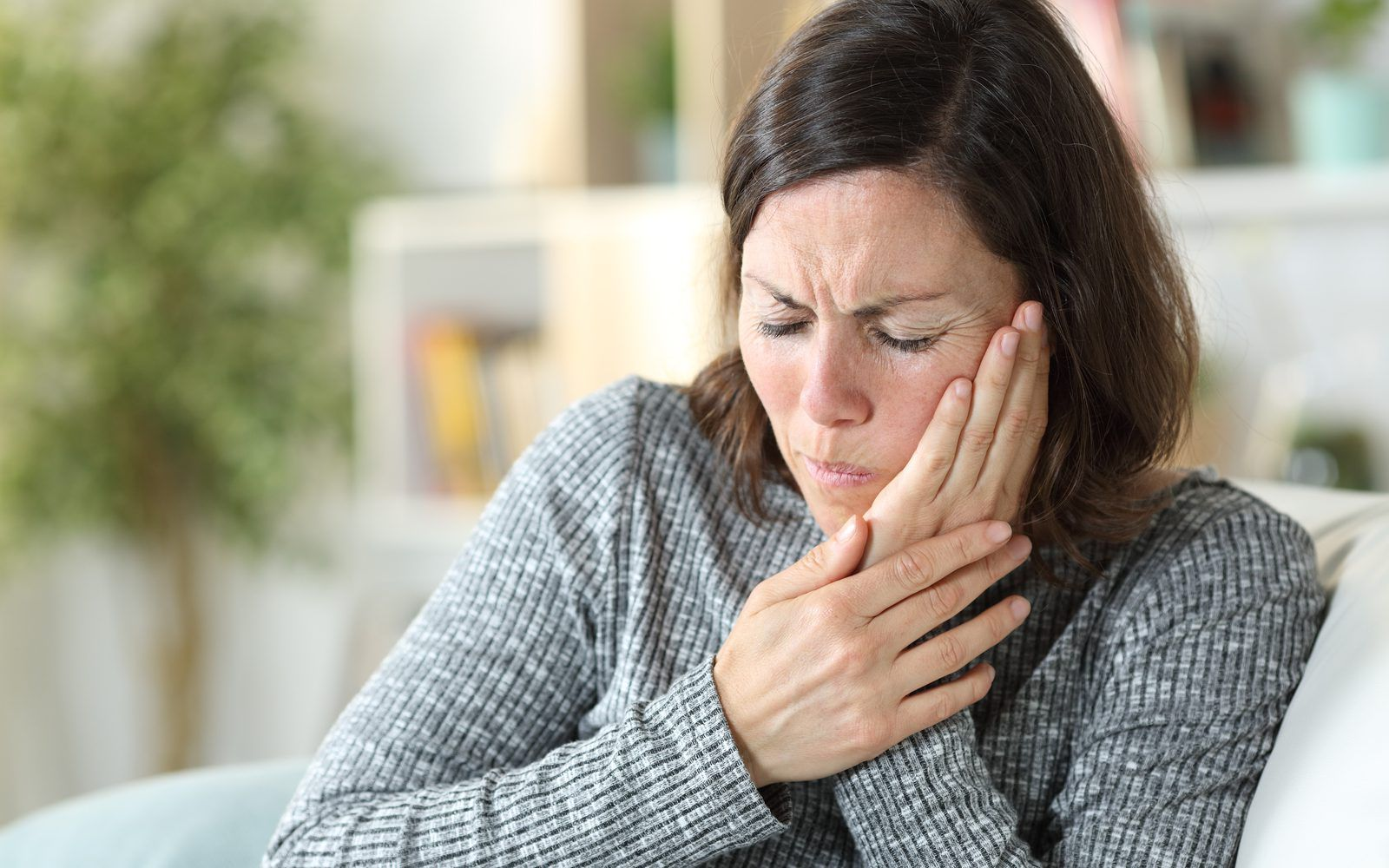 Woman holding face in pain